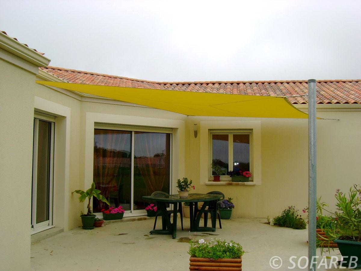Voile dombrage rectangulaire jaune avec qui couvre largement la terrasse dune maison avec baie vitrée