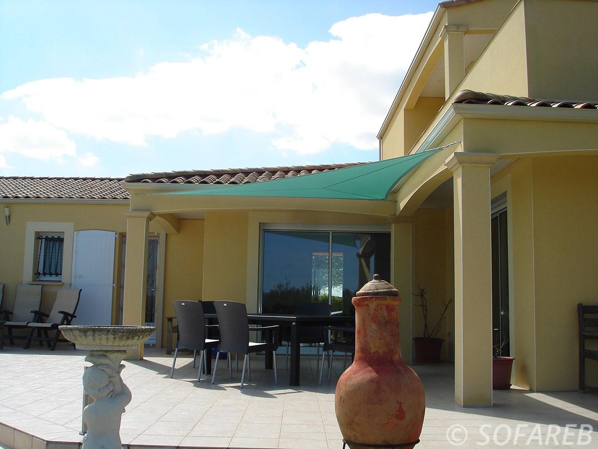 Voile dombrage triangulaire de couleur cyan accrochéeau dessus dune terrasse de maison jaune par Sofareb