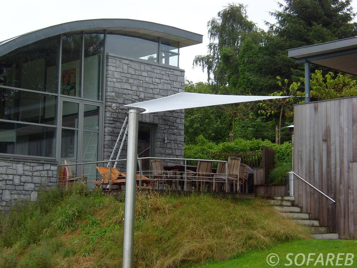 Voile dombrage design et rectangulaire de couleur blanche accrochée à la facade d'une maison en pierre