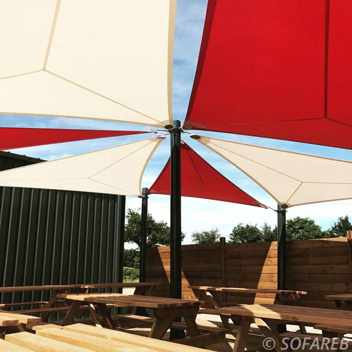 Voiles dombrage triangulaires design rouges et blanches au dessus de la terrasse en bois dun restaurant en Vendée