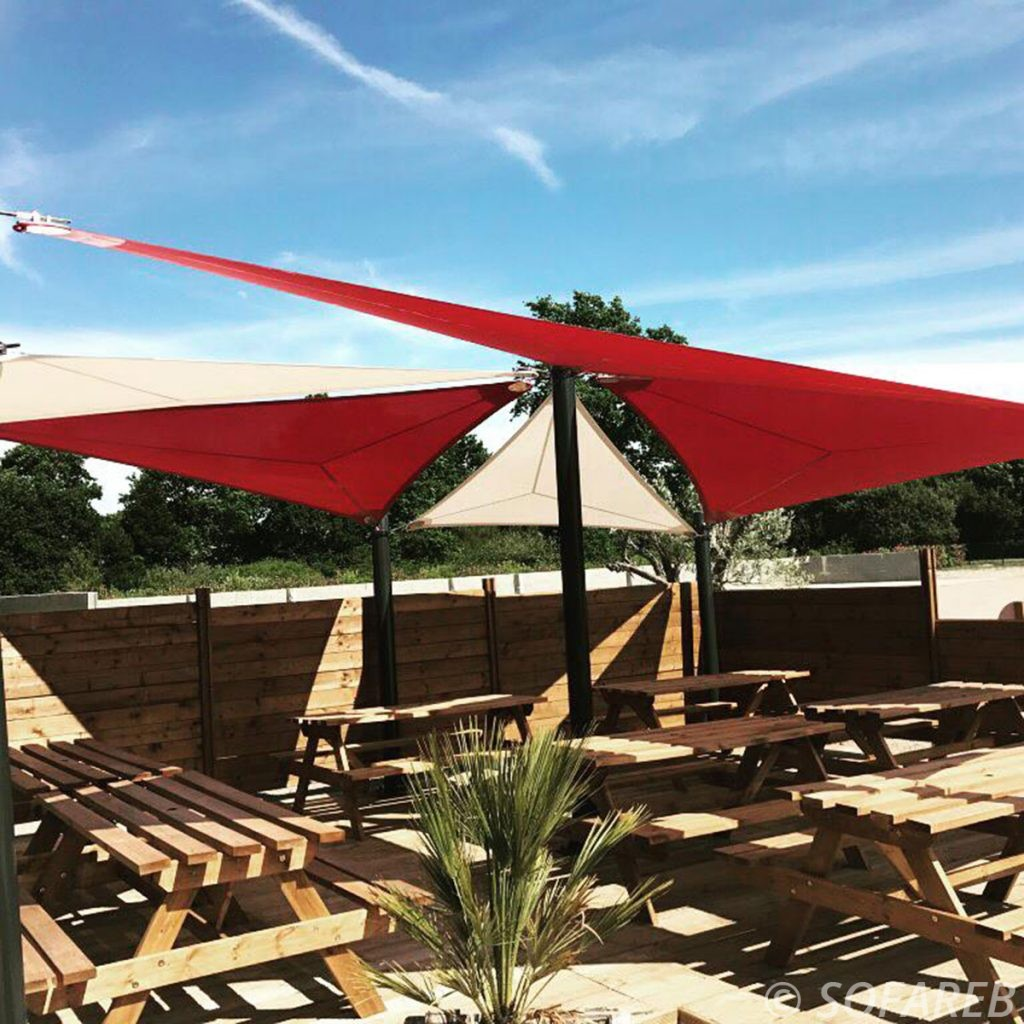 Voiles dombrage triangulaires rouges et blanches réalisées sur-mesure par Sofareb et installées au dessus de la terrasse dun restaurant