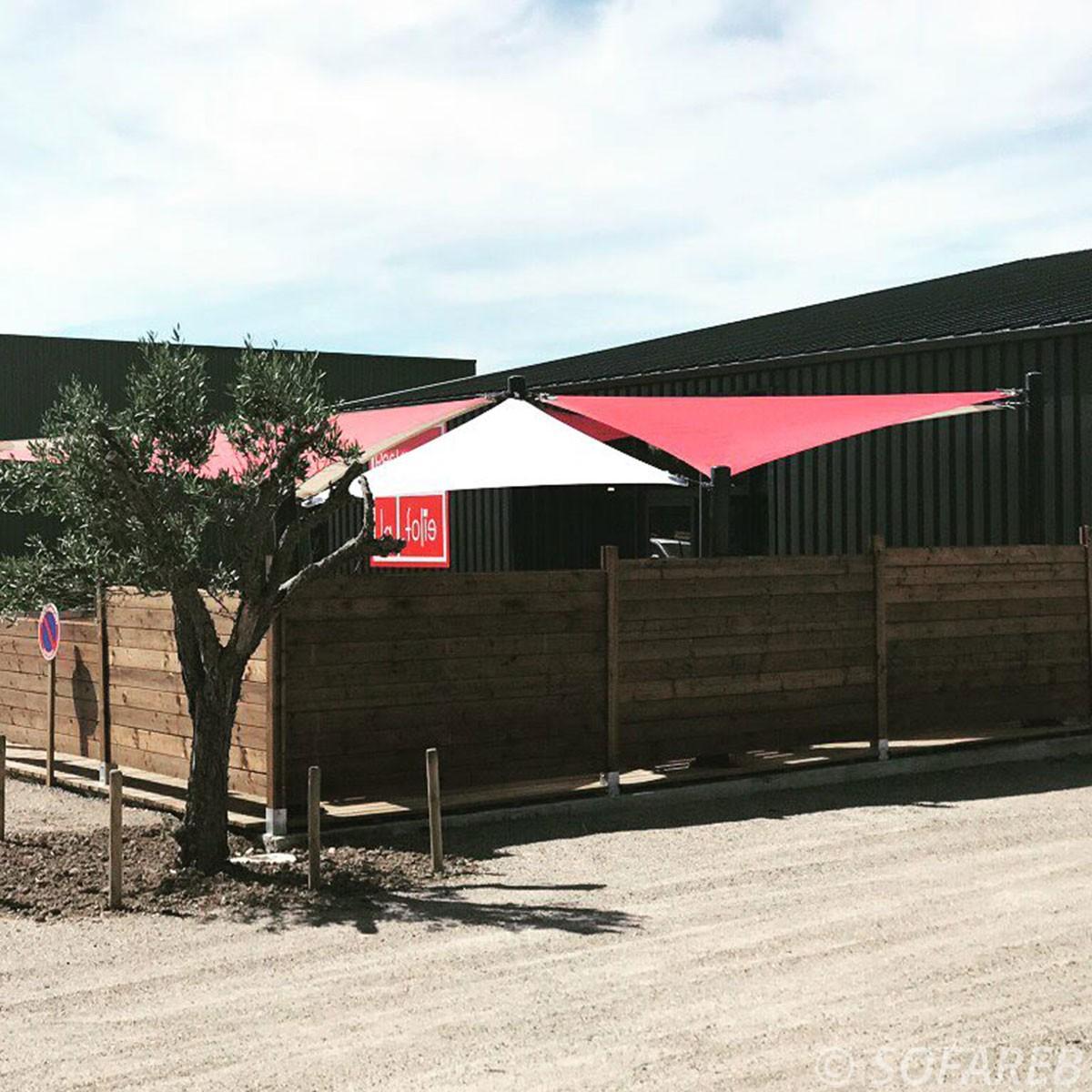 Voiles dombrage triangulaires ani-uv rouges et blanches installées au-dessus dune terrasse de restaurant