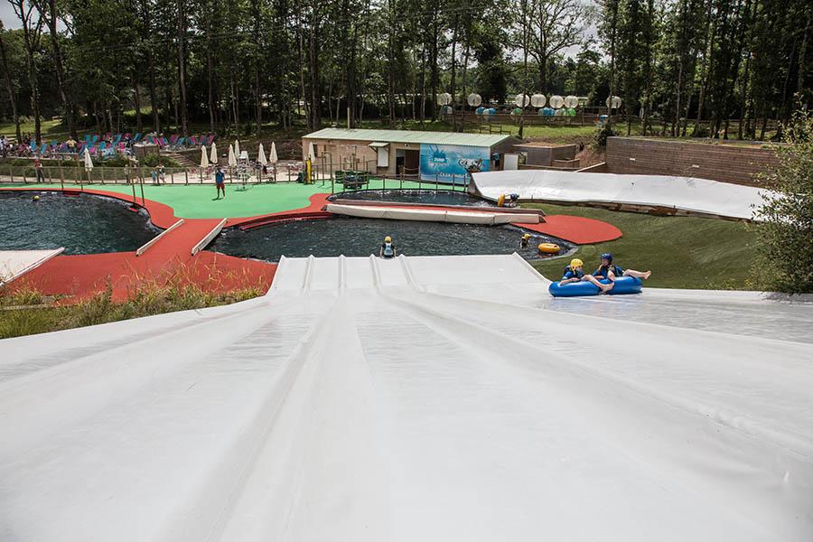 Deux enfants sont dans une bouée et glisse sur le toboggan O'Gliss Park recouvert par des bâches sur-mesures fabriquées et installées par Sofareb en Vendée