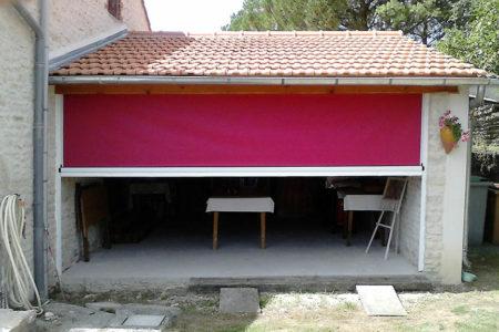 Store vertical rose installé pour abriter le garage d'une maison