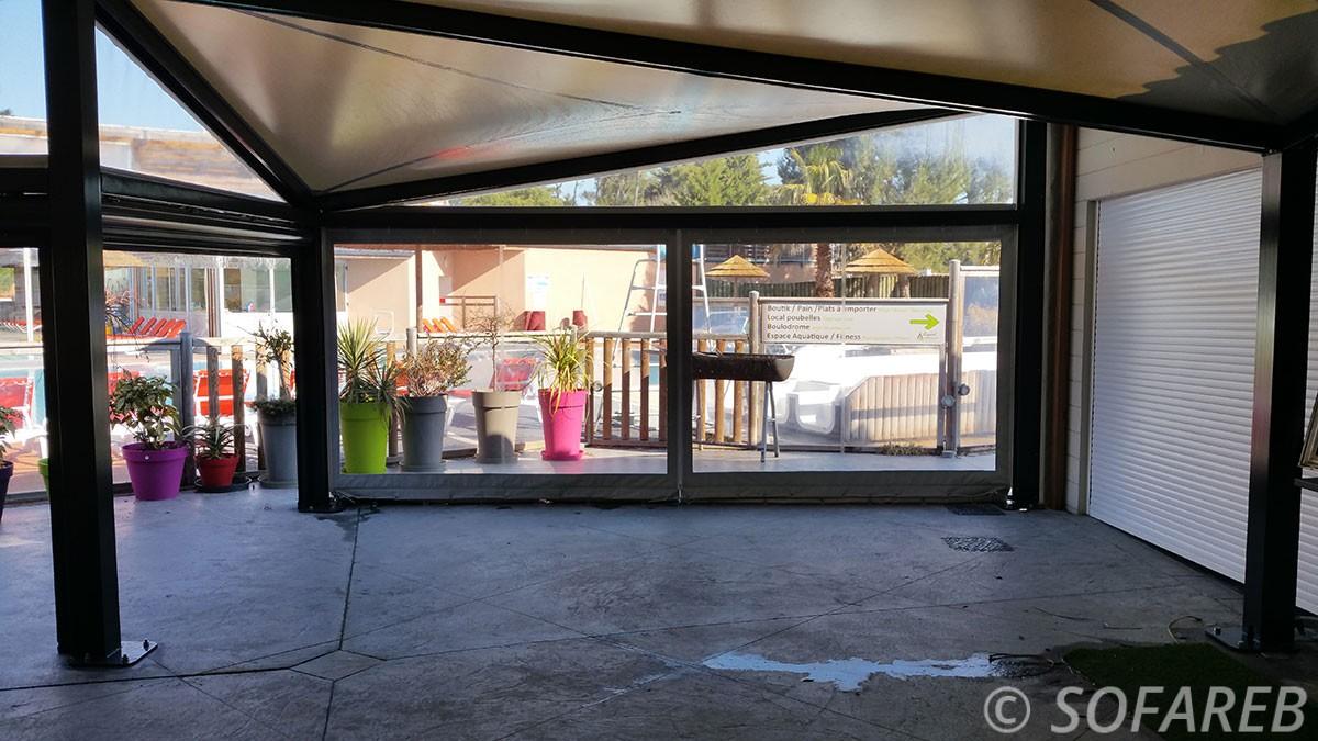pergola vitrée noir autoportante à coté d'une porte de garage, avec beaucoup d'ombre