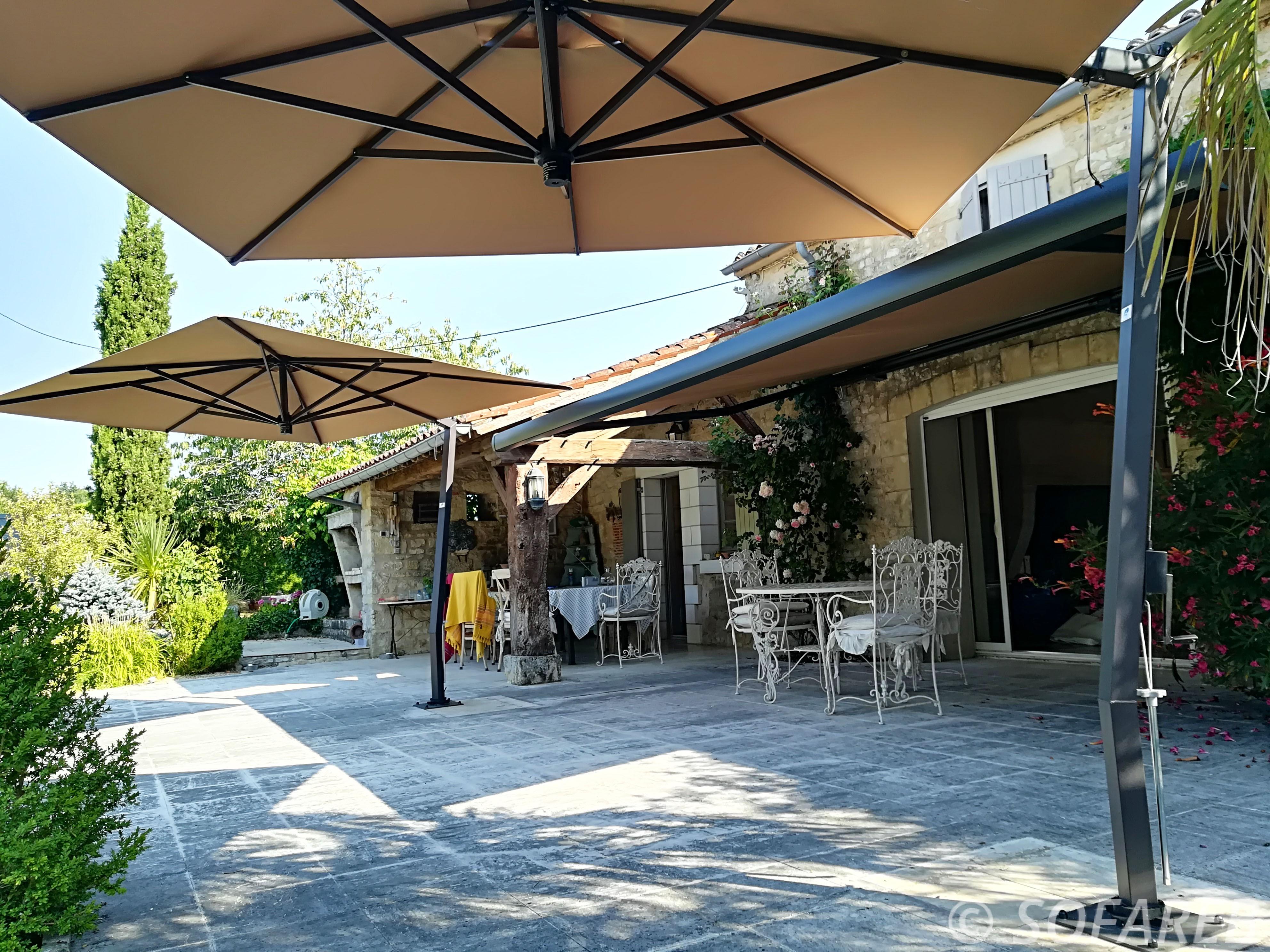 coin ombrage terrasse maison composé de stores et deux parasols