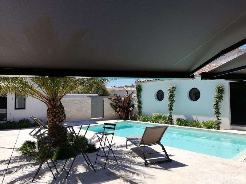 vu du dessous d-un grand store banne marron fonce qui donne sur la cour d-une maison avec piscine