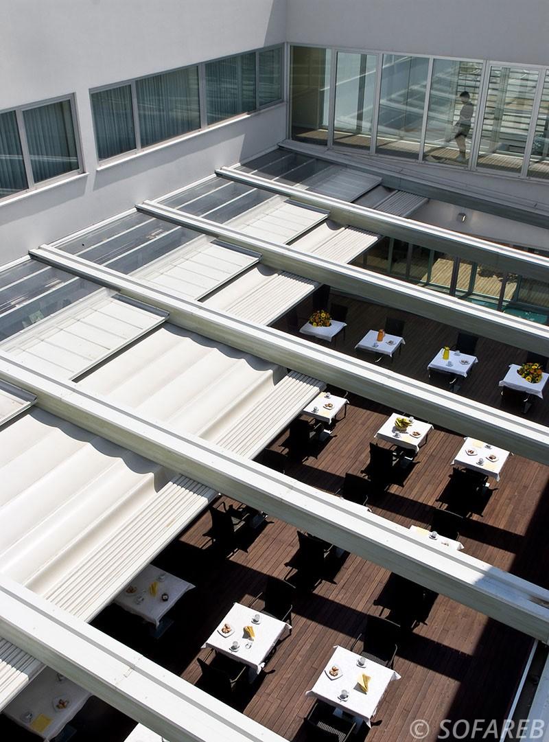 Stores blanc electrique servant de plafond et pouvant s ouvrir completement pour decouvrir la terrasse en pleine air
