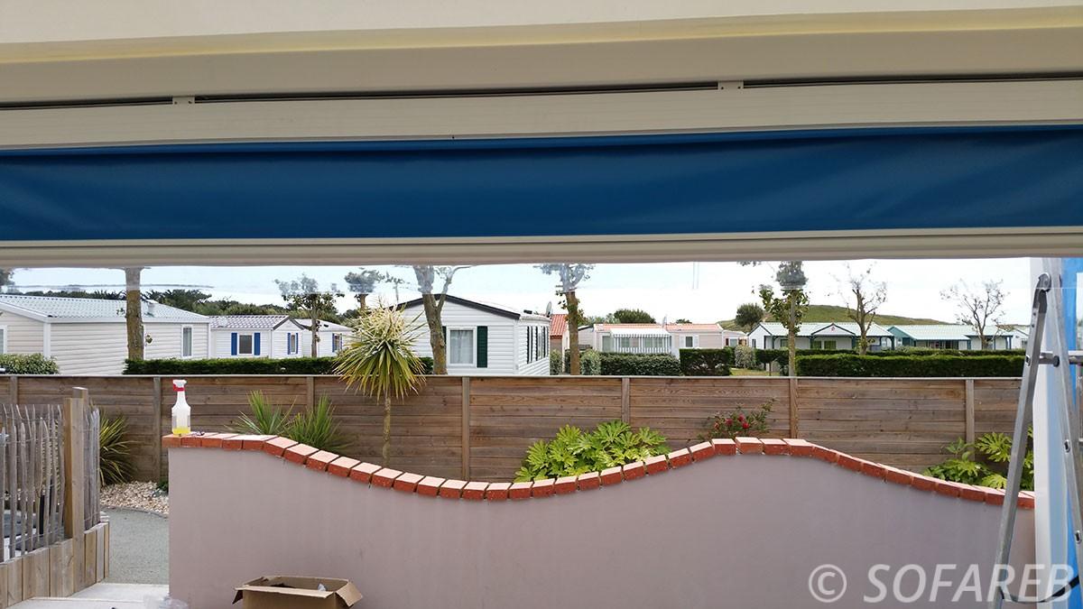 store bleue se deroulant a la verticale et pouvant fermer completement une terrasse exterieure