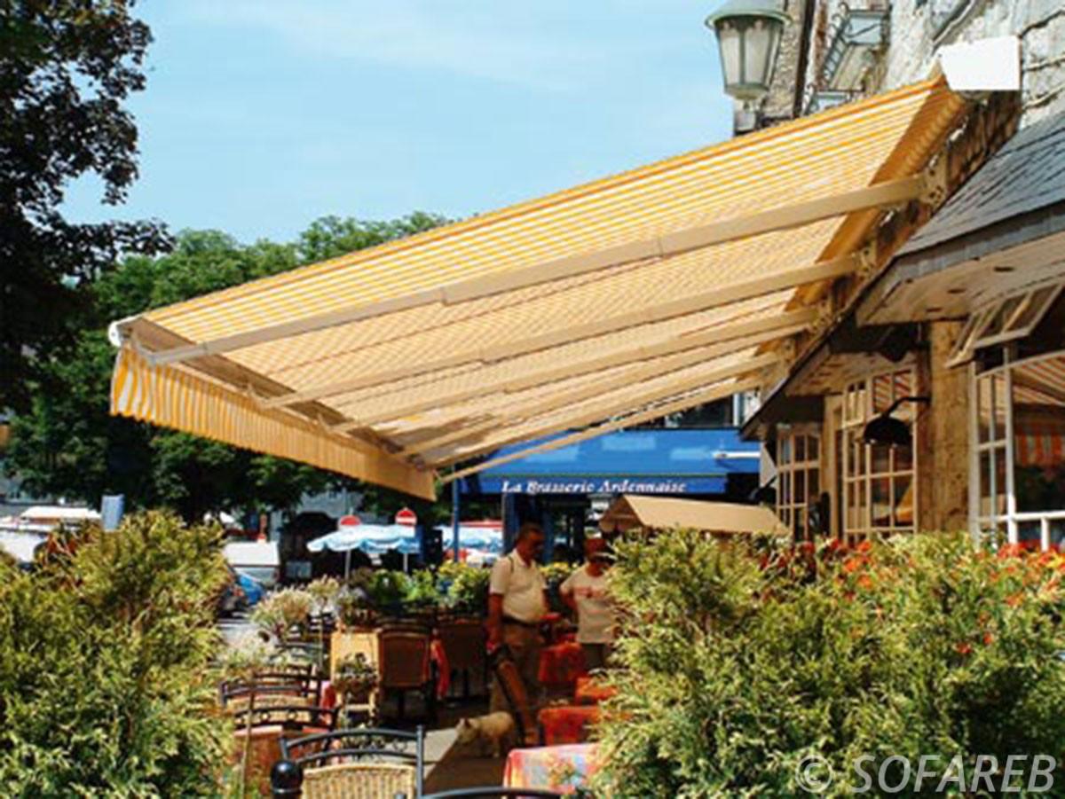 Velum jaune et blanc depliable devanture restaurant et occultant la lumiere du soleil