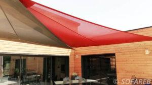 voiles d'ombrages marron et rouge adossées a une maison en bois